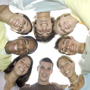 young people in a circle facing downwards towards the camera and smiling